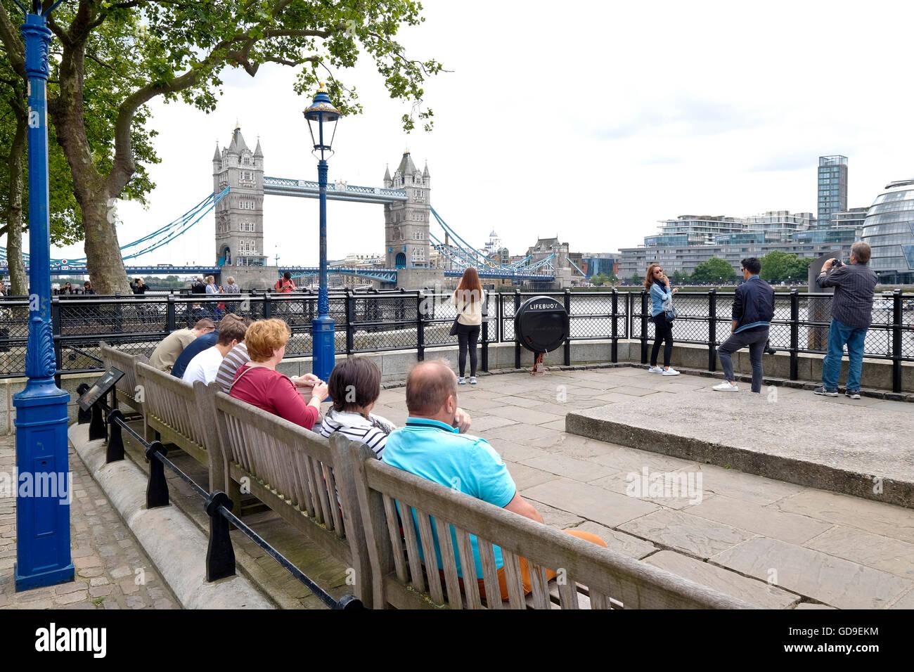 Touristen sitzen auf Bänken Victoria Embankment entlang der Themse. Tower Bridge im Hintergrund und Rathaus Stockbild