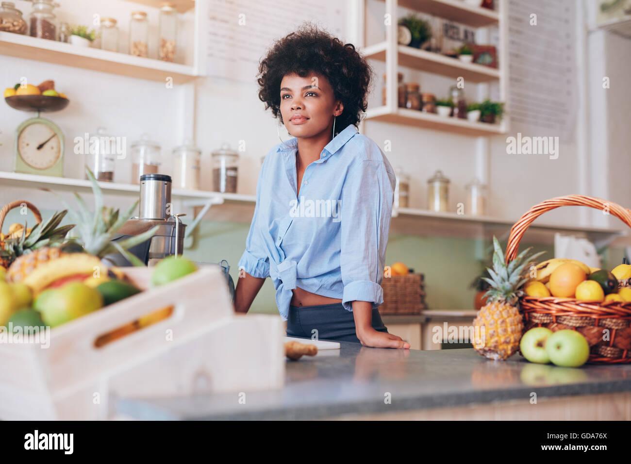 Porträt der attraktive junge Frau am Tresen Saft stehen. Afrikanische Arbeitnehmerin bei Saftbar wegsehen. Stockfoto