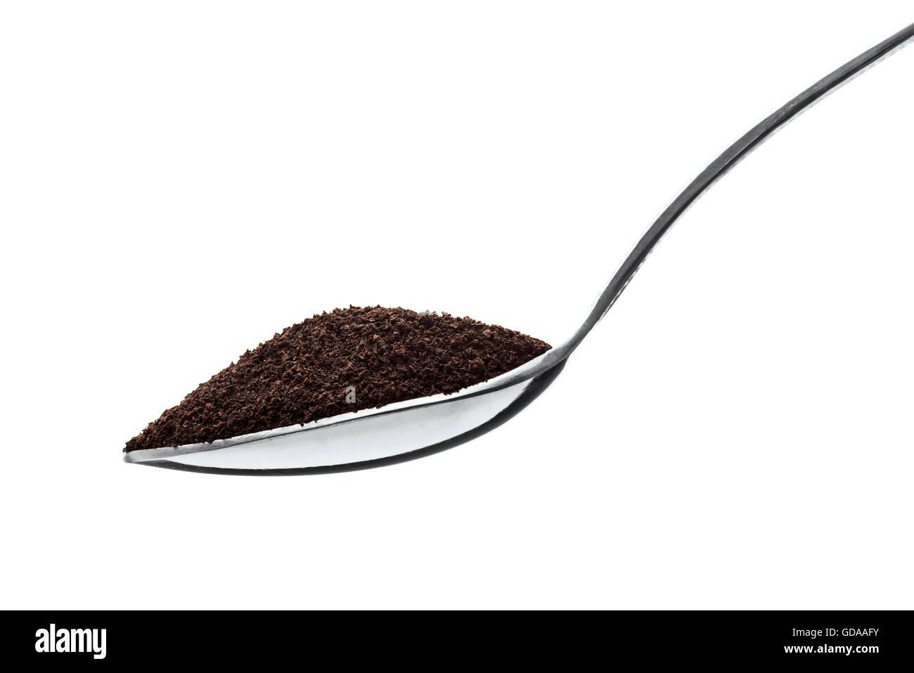 Nahaufnahme der Teelöffel voll von schwarzem Staub Tee, Isolated on White Background Stockbild