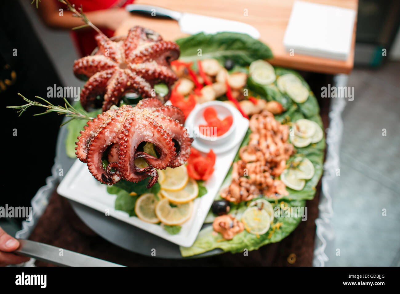 ganz frischen rohen Oktopus auf Schneidebrett mit Zitrone auf rustikalen Holztisch Stockbild