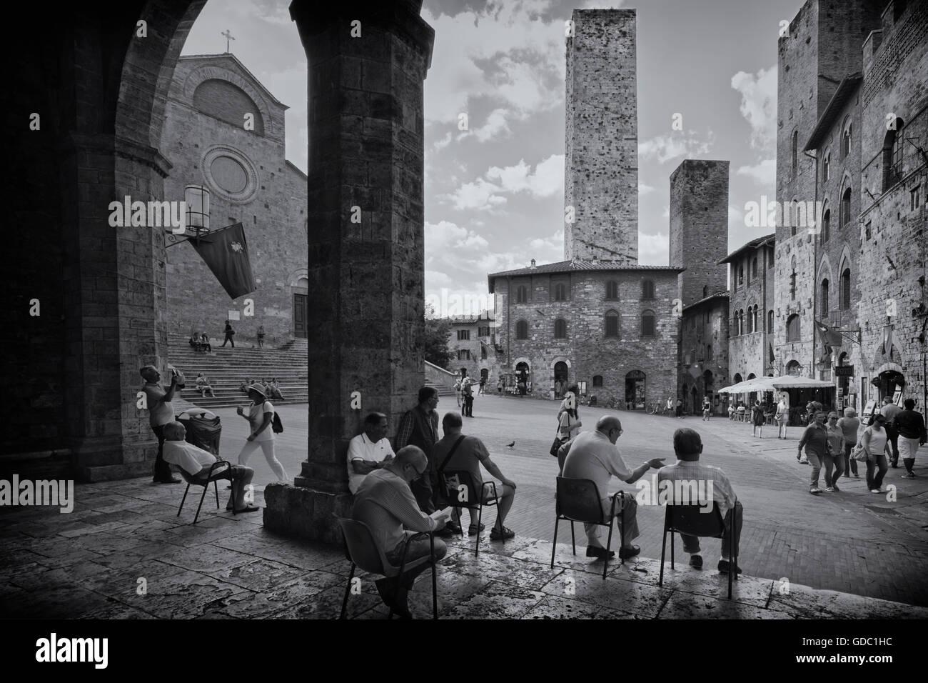 San Gimignano, Provinz Siena, Toskana, Italien.  Einheimischen entspannend auf der Piazza del Duomo. Stockbild