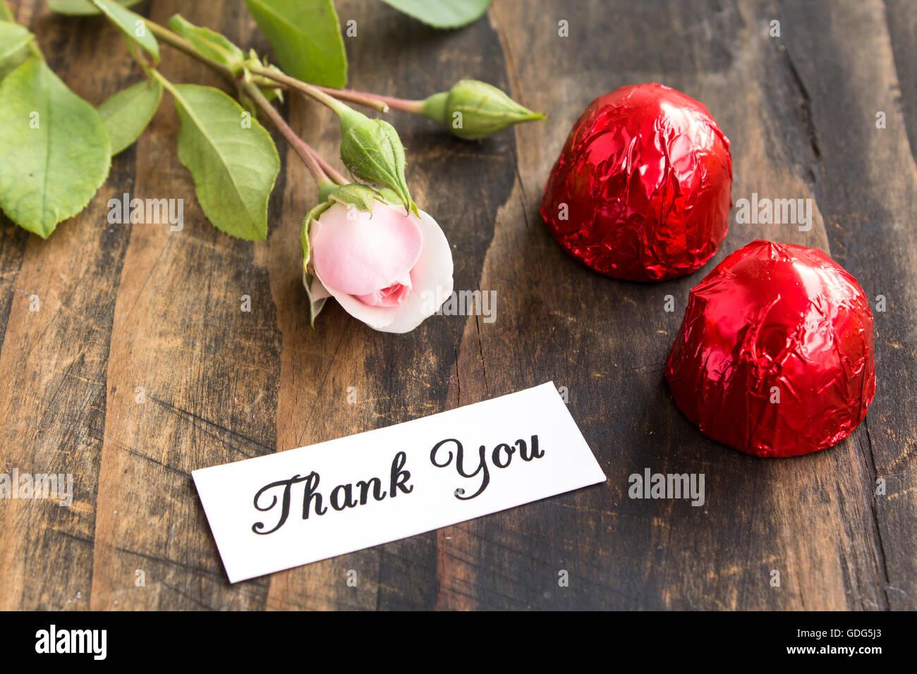 Dankeschön-Karte mit zwei Pralinen und Rose. Stockbild