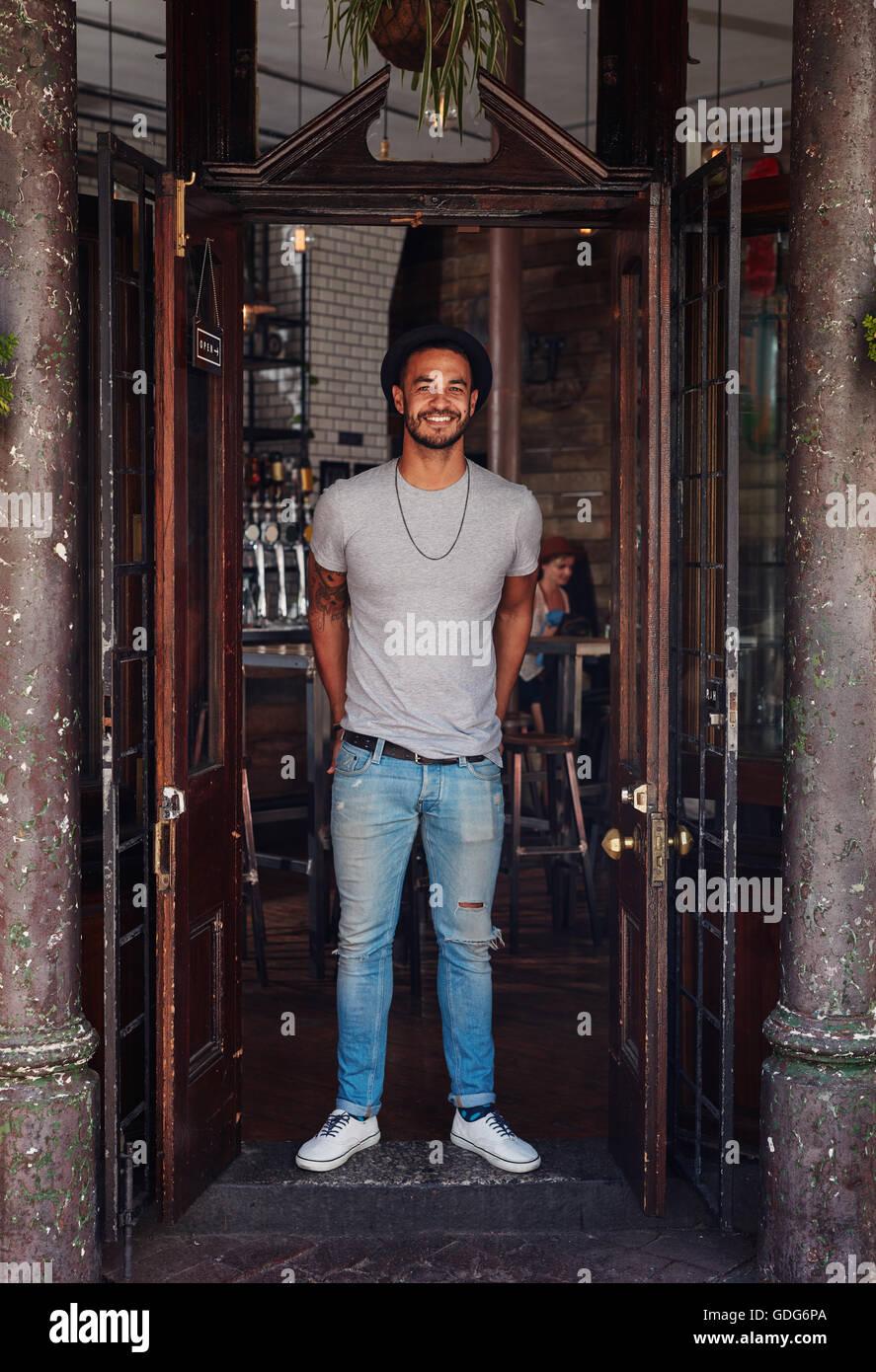 In voller Länge Portrait von stilvollen junger Mann stand an der Haustür von einem Coffee-Shop. Trendige jungen Stockfoto