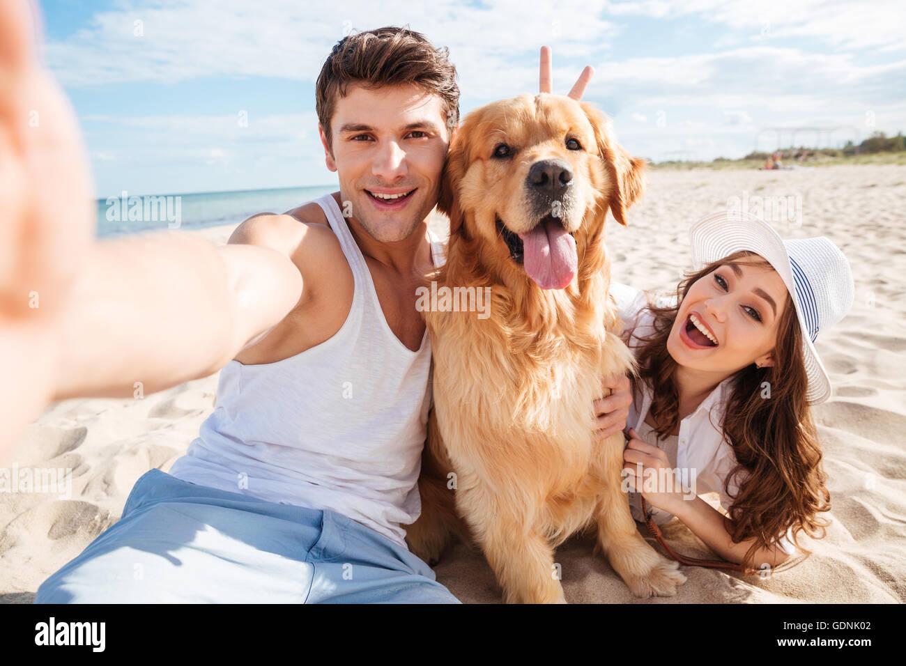 Junges glückliches Paar mit Hund unter einem Selfie am Strand Stockbild