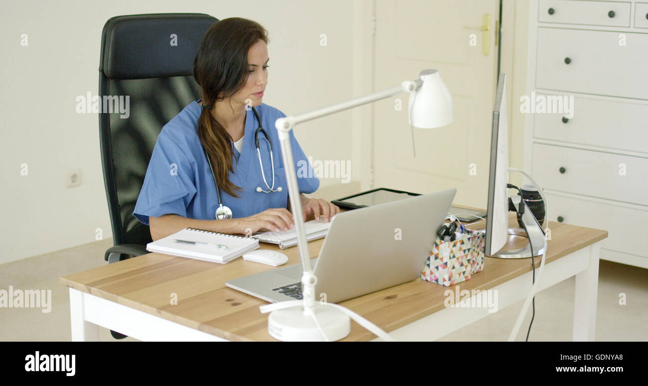 Junge Ärztin Eingabe sitzen in ihrem Büro Stockbild