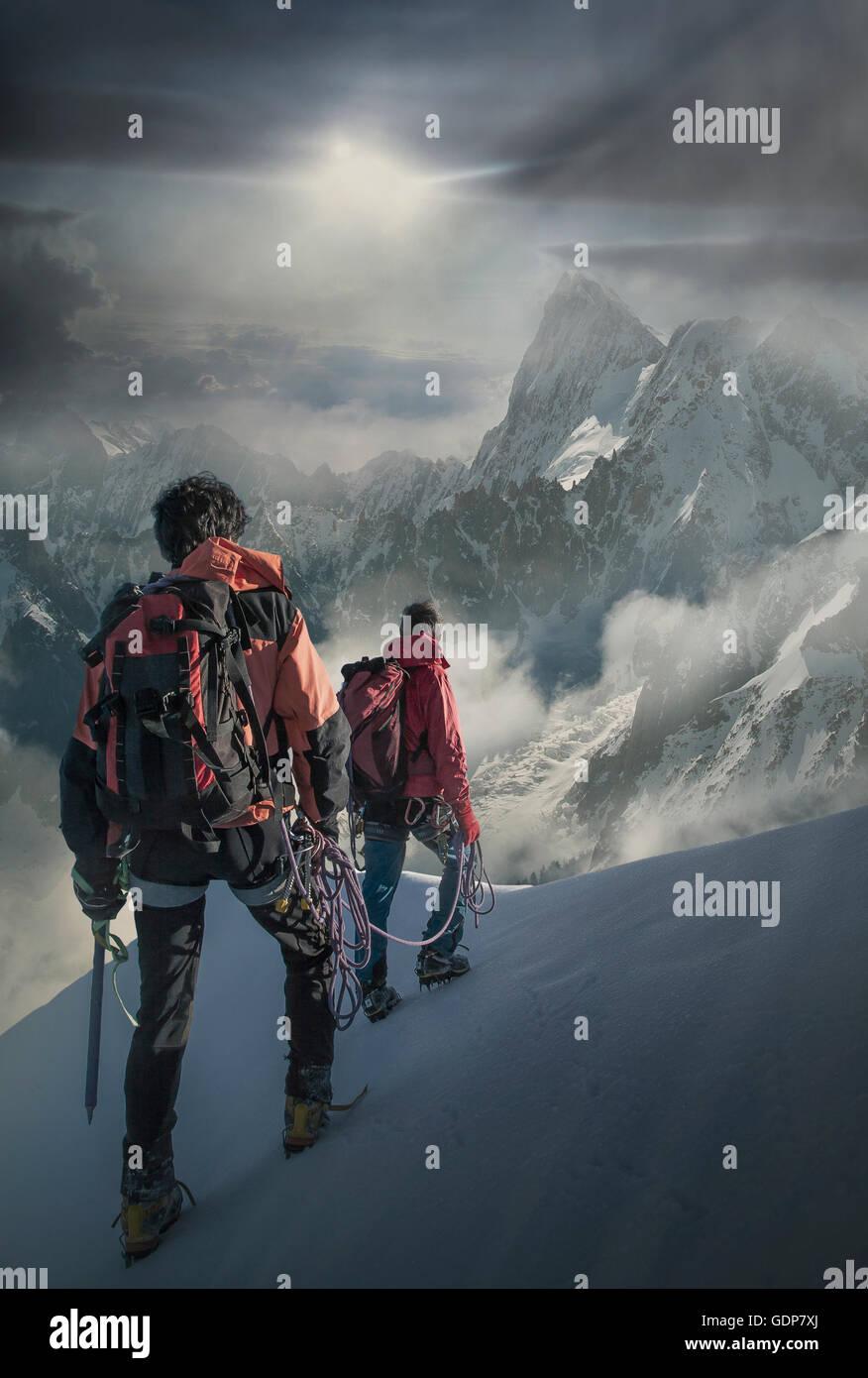 Zwei Bergsteiger auf einen verschneiten Hang beobachten den Grand Jorasses im Mont-Blanc-Massiv, Chamonix, Frankreich Stockbild