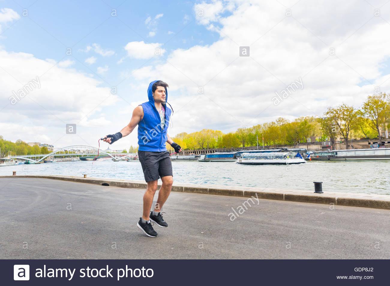 Junger Mann, Bewegung in der Natur, mit Springseil, neben Fluss überspringen Stockbild