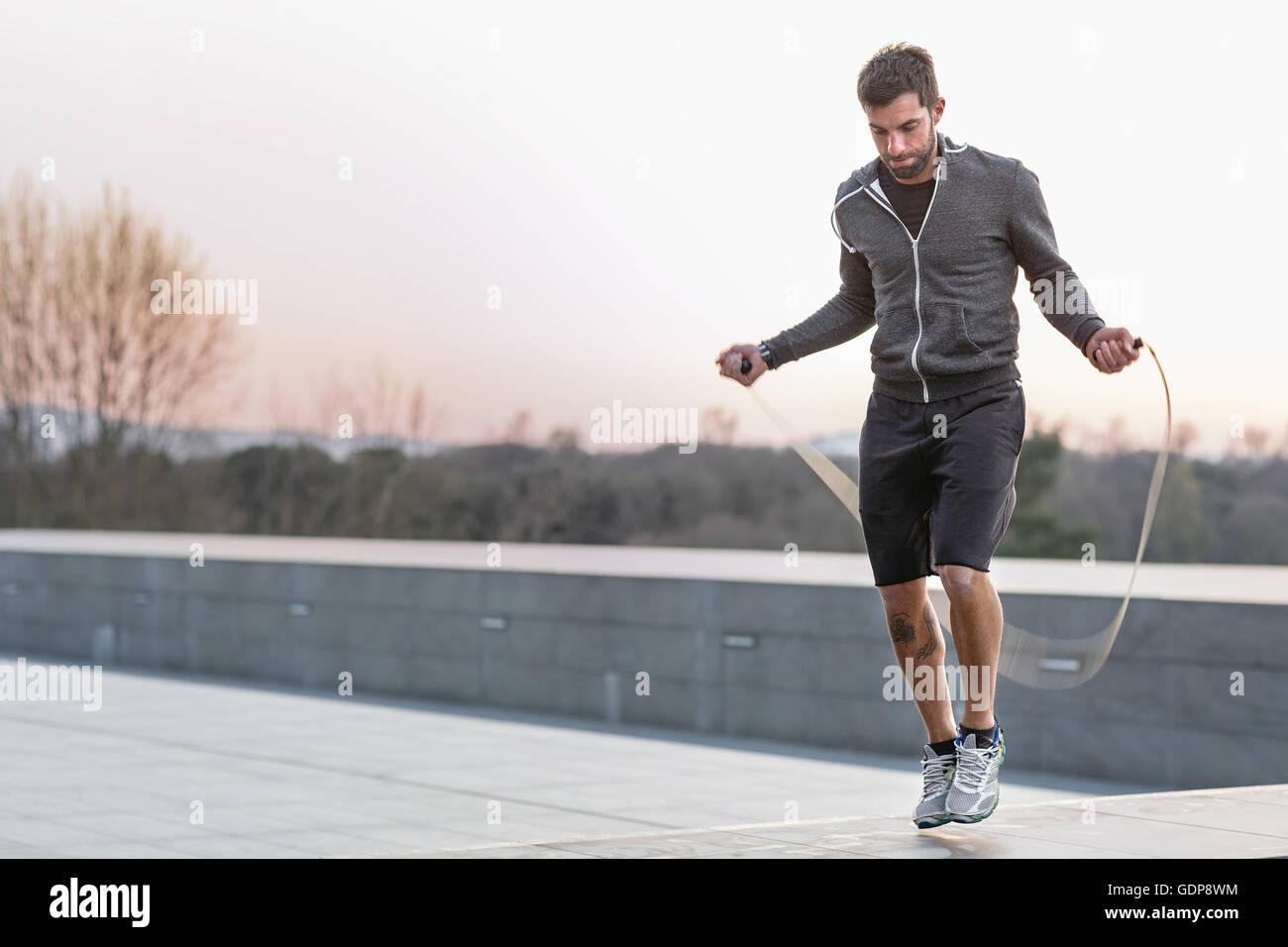 Mitte erwachsenen Mannes im Freien, überspringen mit Springseil Stockbild