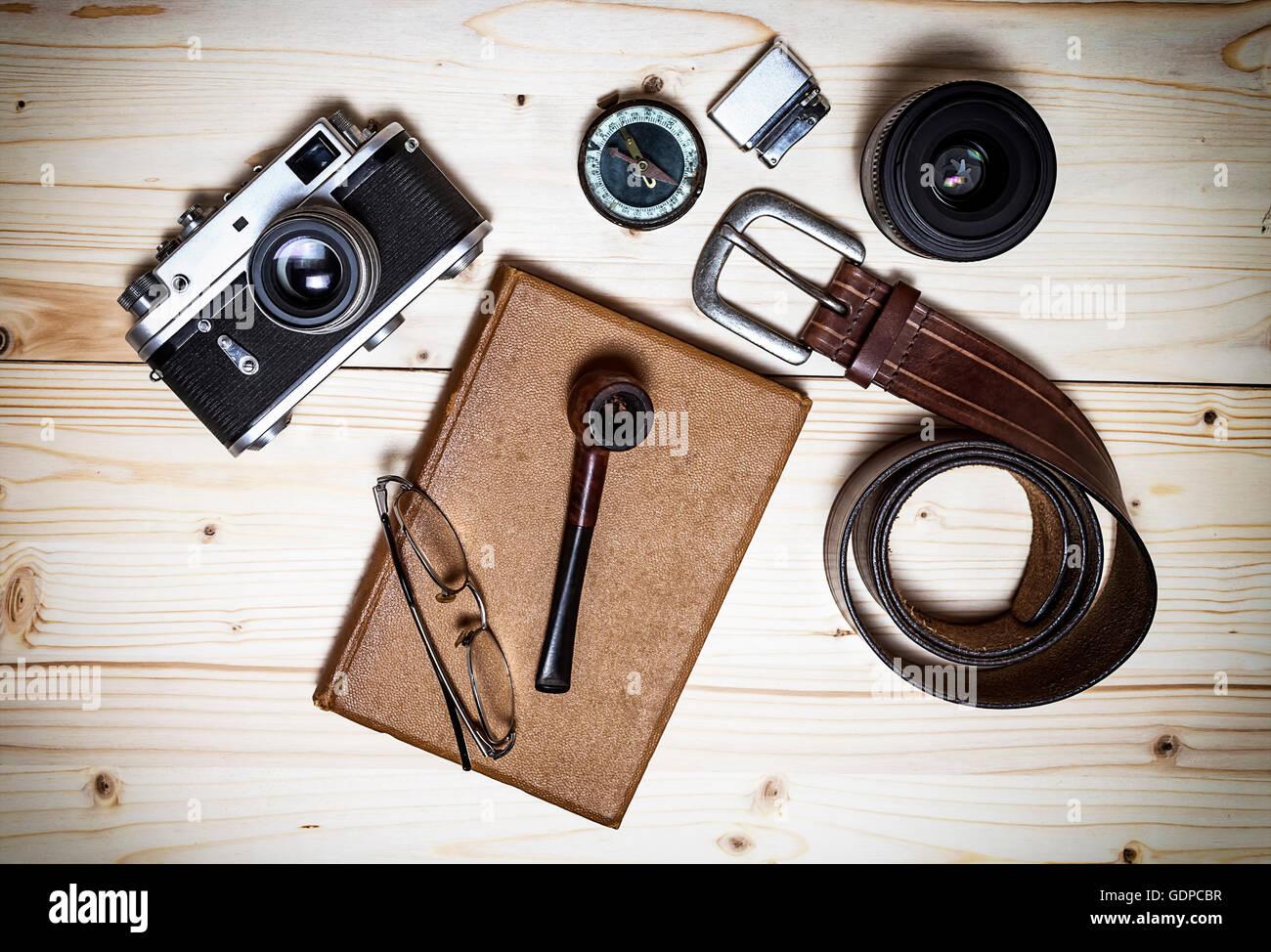 Stillleben mit Retro-Objekt. Buchen Sie mit alten Kompaktkamera, Kompass, Feuerzeug, Gürtel, Brille, Rohr, Stockbild
