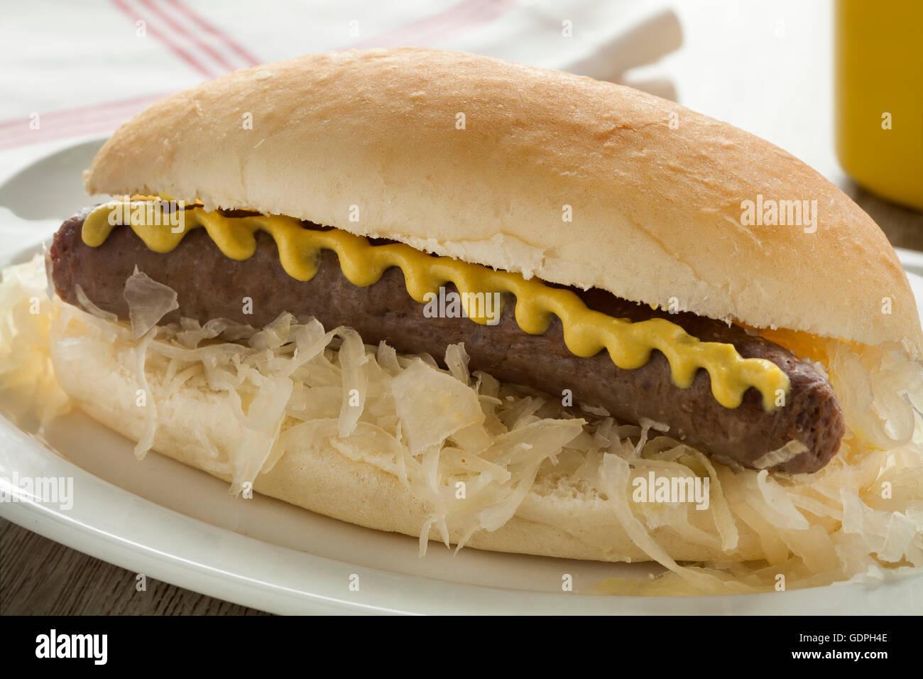 Weißen Brötchen mit Sauerkraut, Wurst und Senf hautnah Stockbild