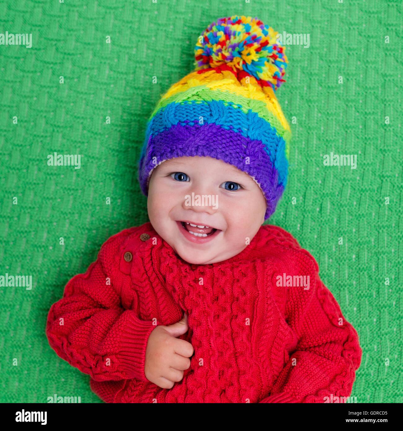 detailed look 092bf 5b774 Niedliche Baby in warme gestrickte Wollmütze auf einer roten ...