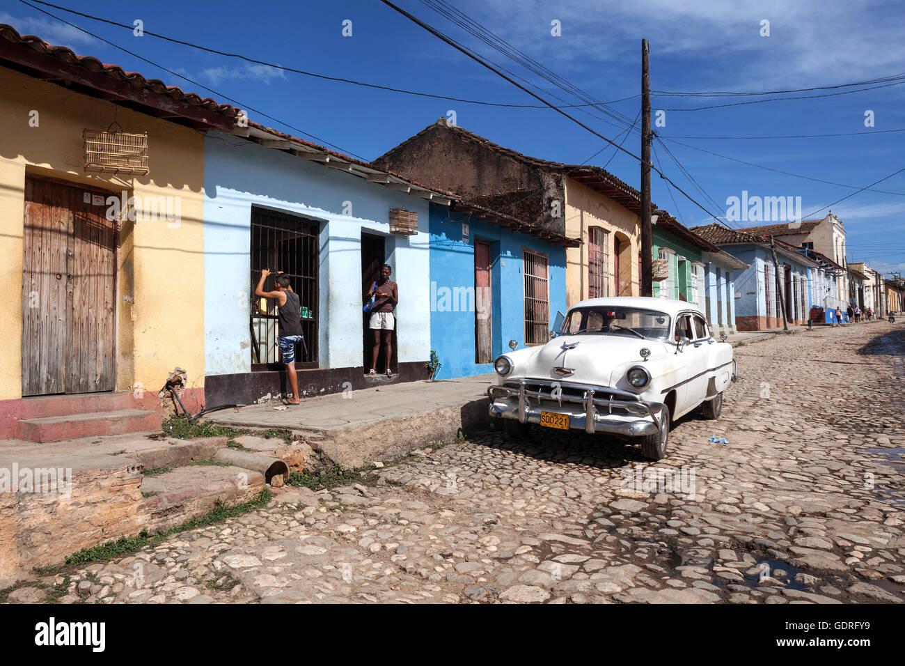 Straße Landschaft, typische Straße mit Kopfsteinpflaster, bunten Häusern und Oldtimer, historische Stockbild