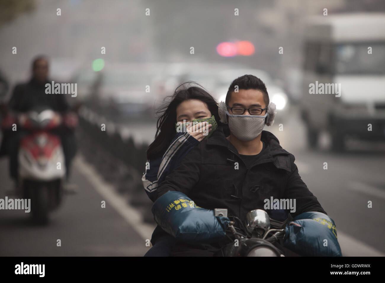 Ein paar fährt auf einem Motorrad unter einer grauen Wolke der Smog in der Innenstadt von Stockbild