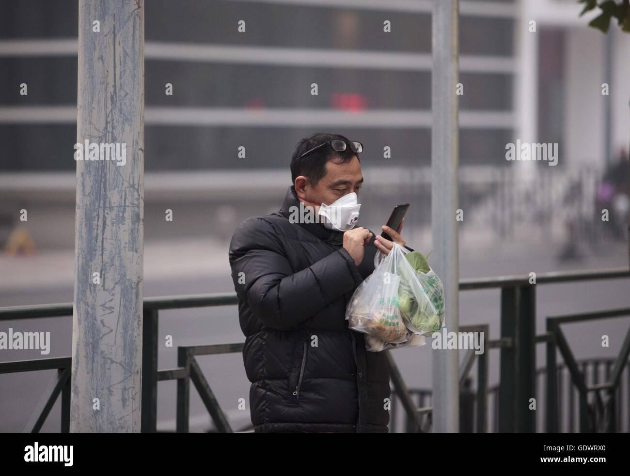 Ein Mann trägt einen Mundschutz nutzt sein Handy unter einer grauen Wolke der Smog in der Innenstadt von Stockbild