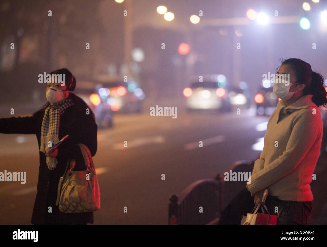 Zwei Frauen tragen Mundschutz warten auf Taxi unter einer grauen Wolke der Smog in der Innenstadt von Stockbild