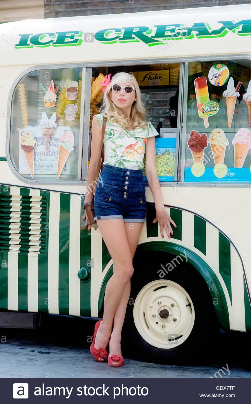 Frau trägt eine Vintage Hawaii Hemd und Jeans Shorts lehnt sich gegen einen traditionellen 50er Jahre Stil Stockbild