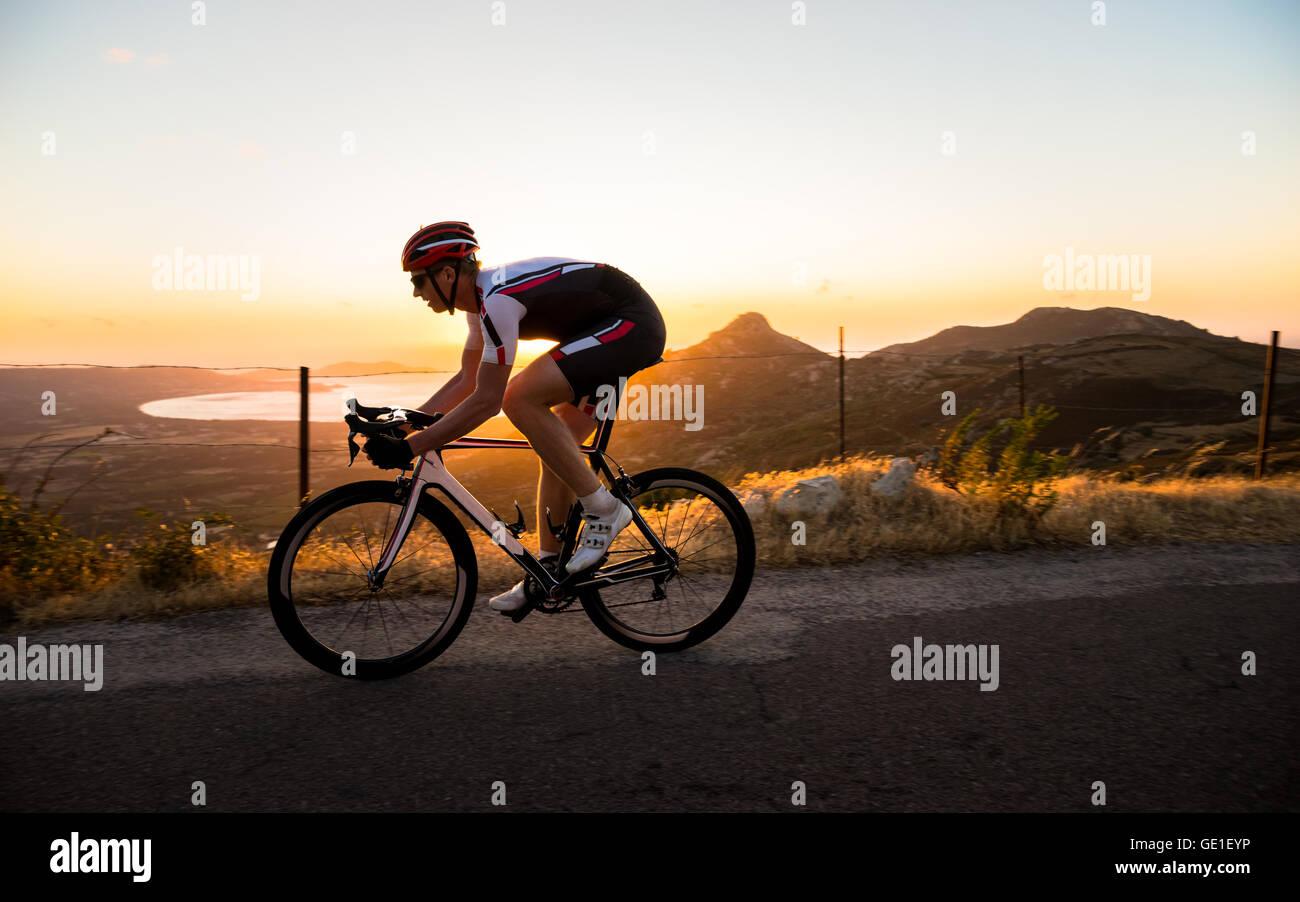 Mann Radfahren bei Sonnenuntergang, Korsika, Frankreich Stockfoto