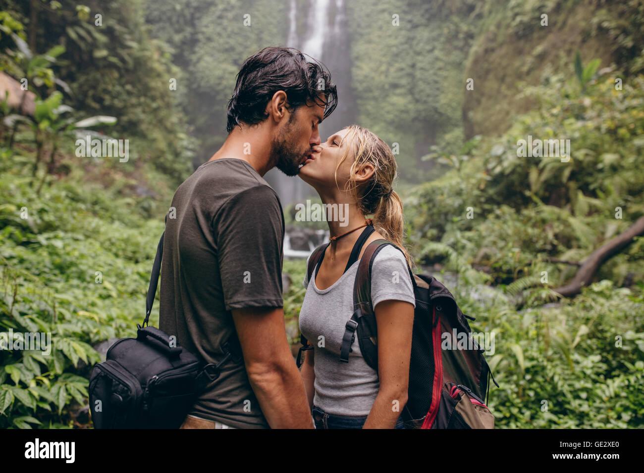 Aufnahme des jungen Liebespaar stehend im Wald küssen. Paar in Liebe küssen in der Nähe von einem Stockbild