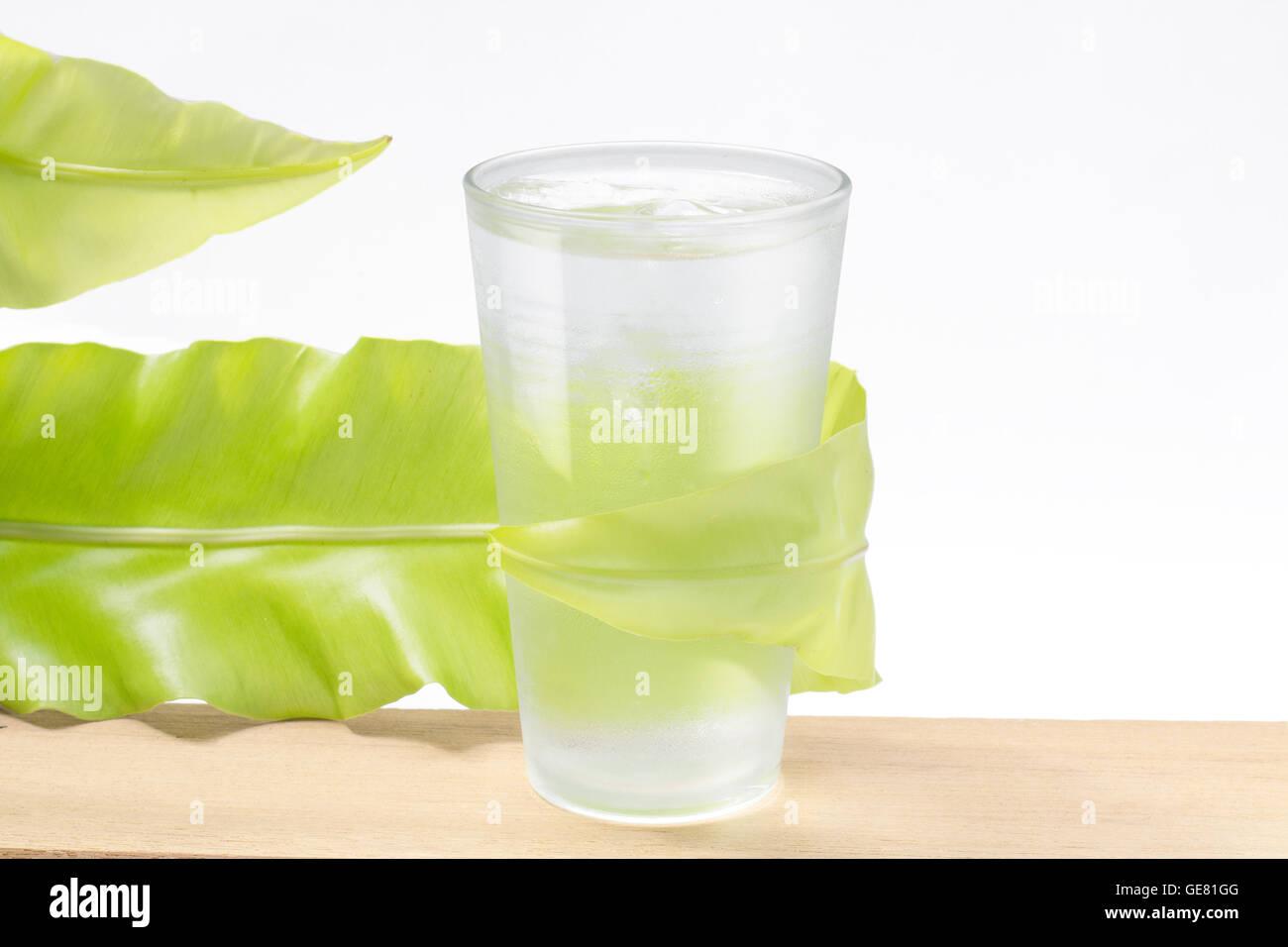 frisches Wasser im Glas mit grünen Blatt auf weißem Hintergrund Stockbild