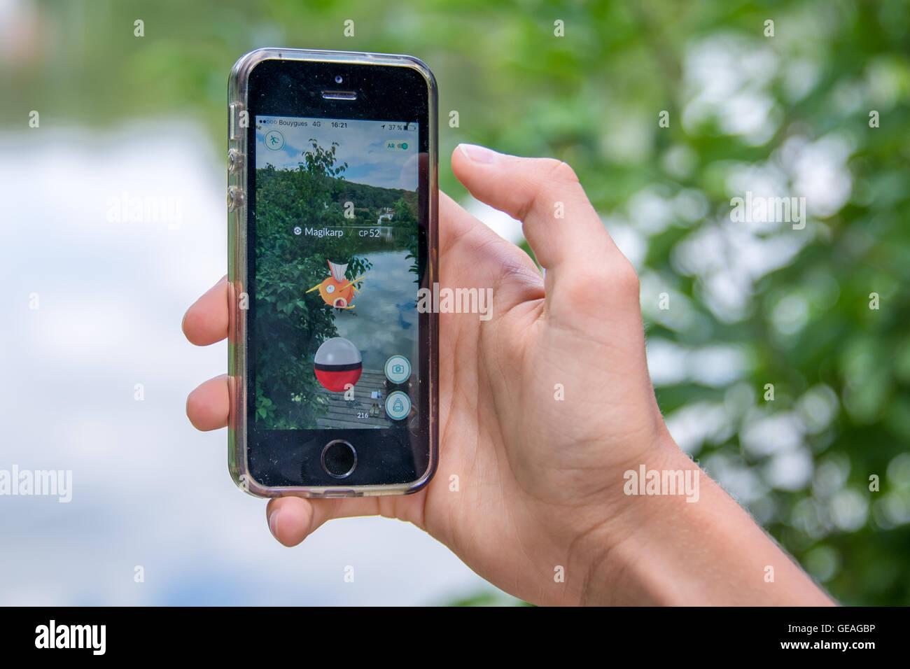 Meudon, Frankreich. 24. Juli 2016. Apple iPhone5s mit Pokemon Go Anwendung, Hände eines Teenagers, spielt in Stockbild