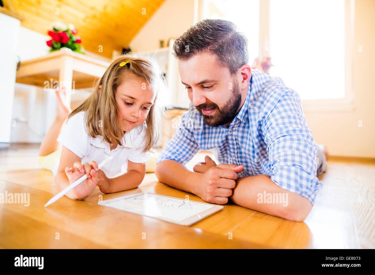 Vater und Tochter auf Boden liegend, gestützt auf digital-Tablette Stockbild