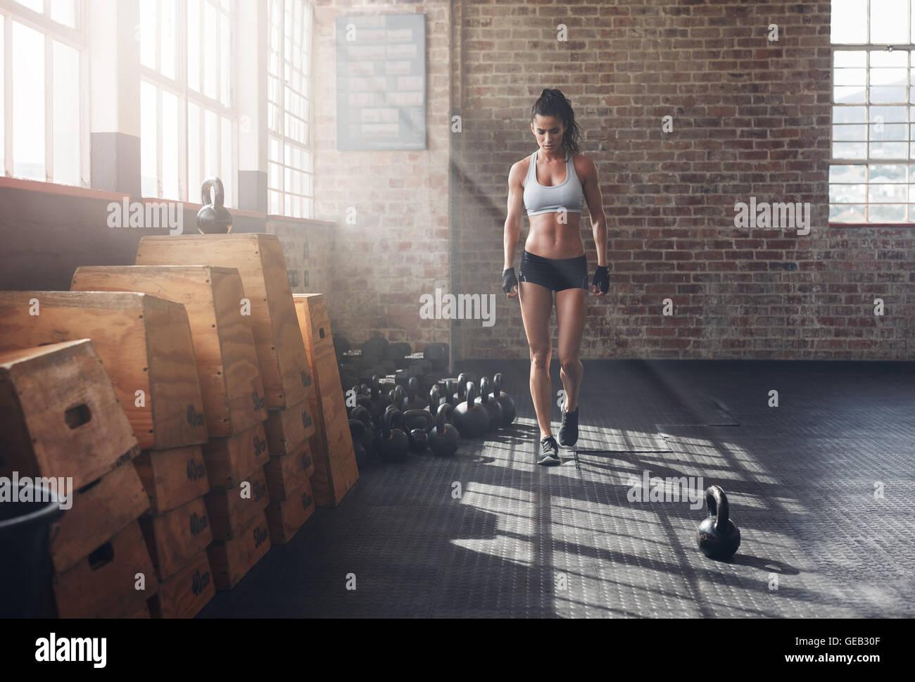 Voller Länge Aufnahme Fitness Frau zu Fuß in die Turnhalle mit Wasserkocher Glocke am Boden. Aufwärmen Stockbild