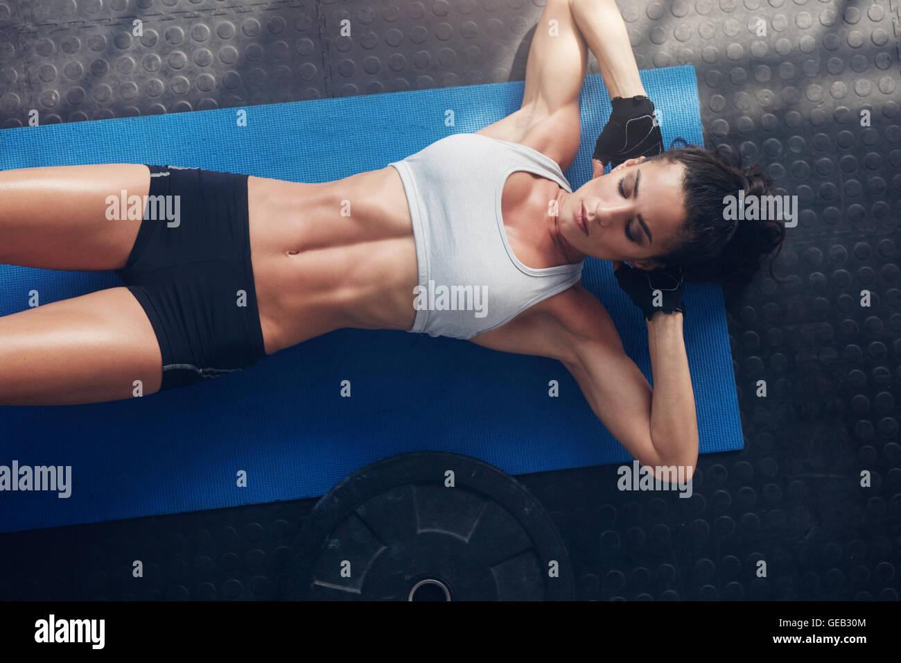 Draufsicht der Frau Ausübung auf Yoga-Matte. Weibliche liegend Gymnastikmatte mit ihren Händen hinter dem Kopf im Stockfoto