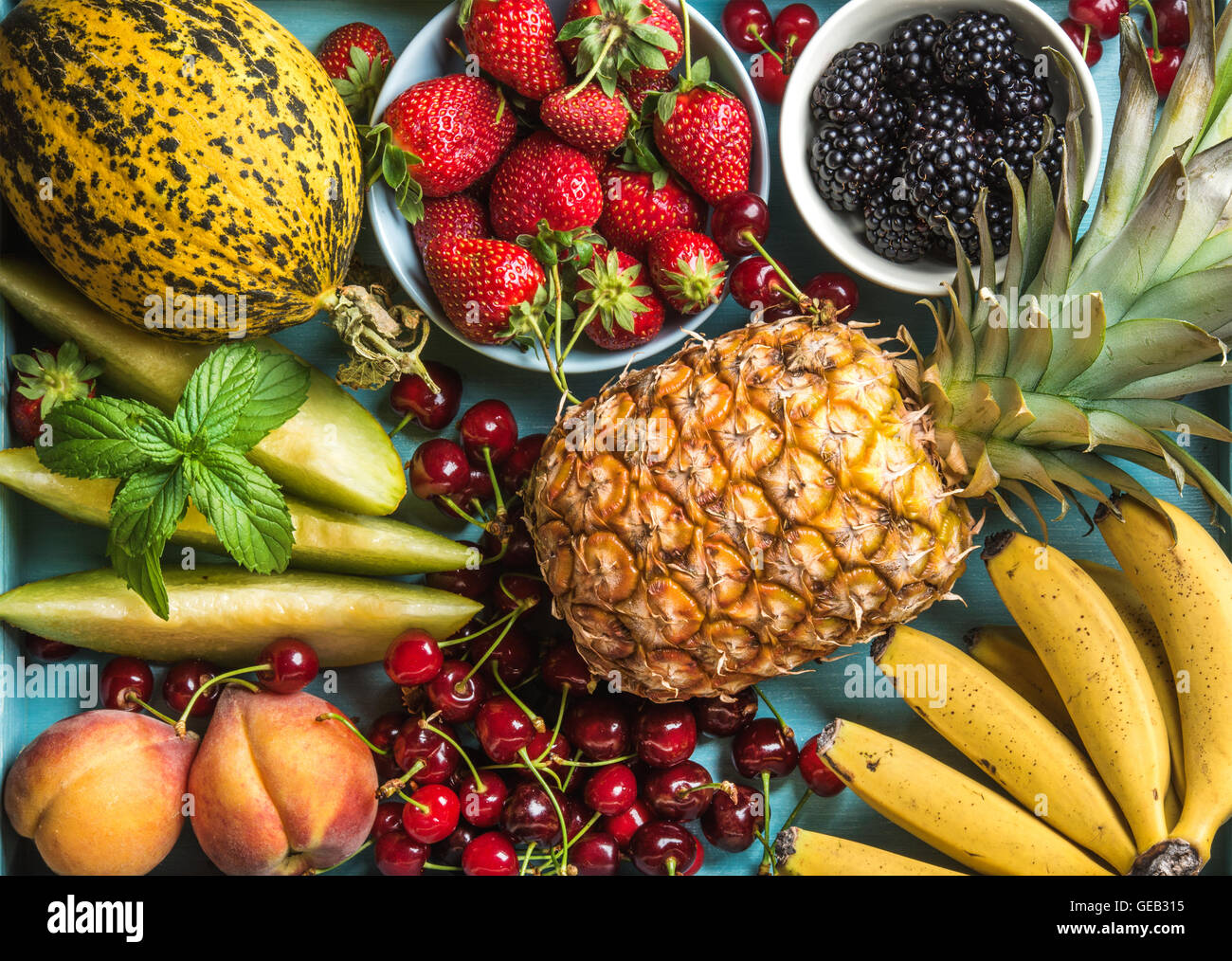 Gesunden Sommer Obstsorte. Süße Kirschen, Erdbeeren, Brombeeren, Pfirsiche, Bananen, Melonenscheiben und Stockbild