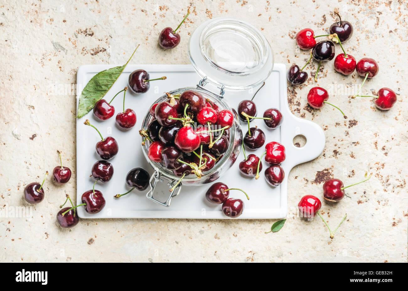 Sweet cherry in glas auf tafel über konkrete hintergrund stockfoto