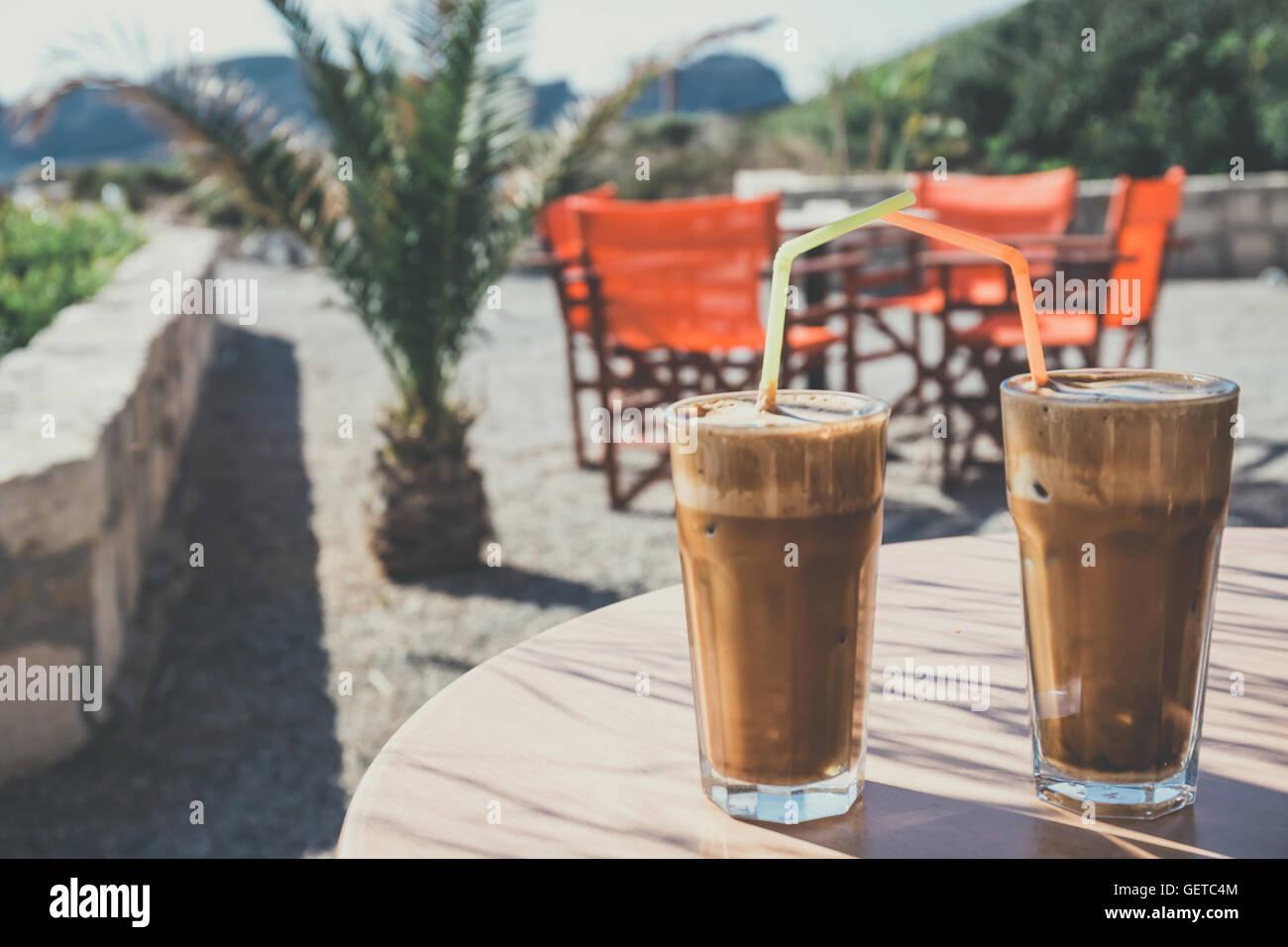 Kaffee Frappe, griechische Küche auf dem Tisch am Strand, Vintage ...