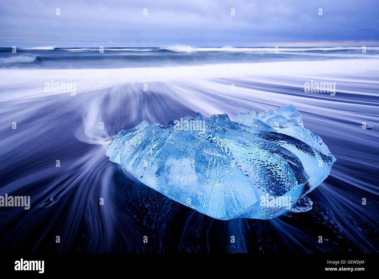 Wellen Waschen um einen kleinen Eisberg am Strand am Jökulsárlón in Island. Stockfoto