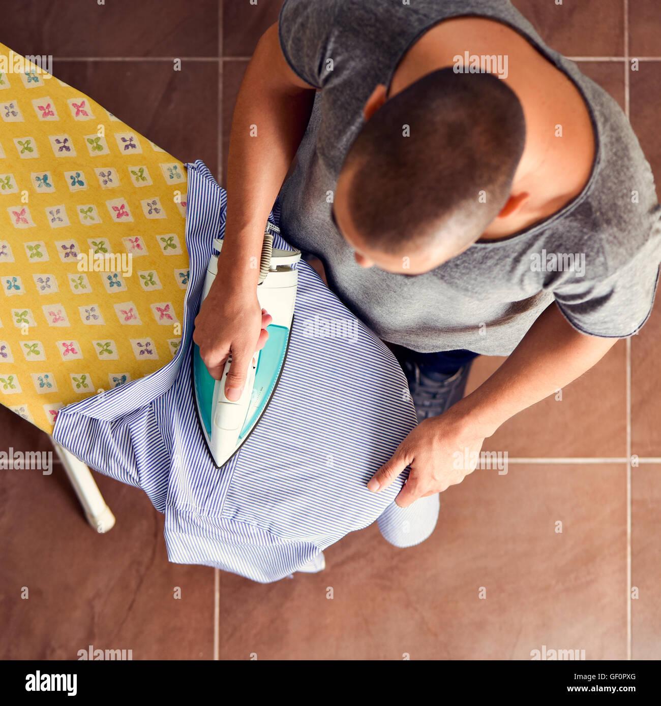 High-Angle Shot von einem jungen Mann ein gestreiftes Hemd mit Hosenbügler auf dem Bügelbrett Bügeln Stockbild