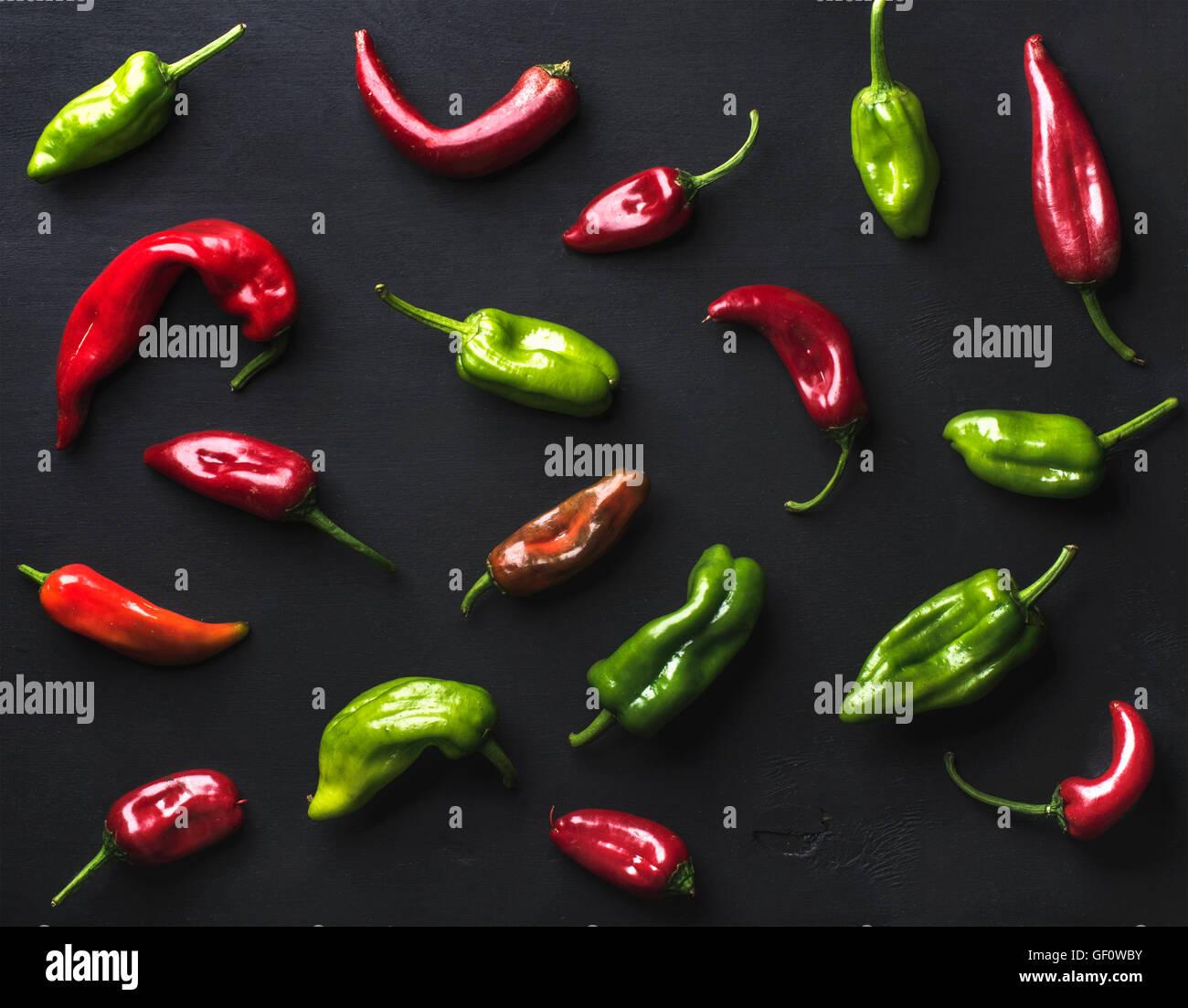 Muster von kleinen bunten hot Chili Peppers auf schwarzem Hintergrund Stockbild