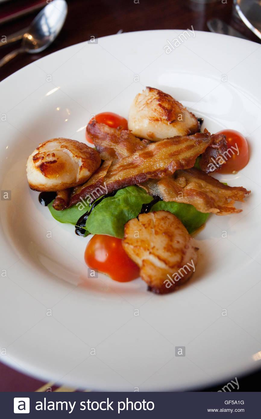 Ein Anfängerkurs von Hand getaucht Jakobsmuscheln mit Speckscheiben knusprigem Speck und Salat serviert in Stockbild