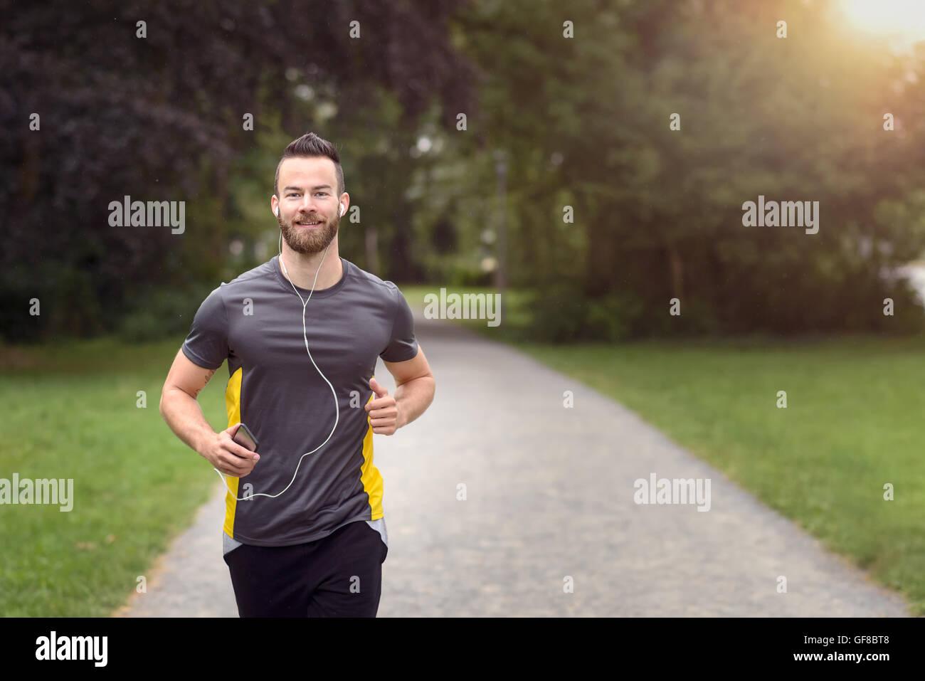 Fit bärtige junge Mann joggen durch den Park, das Anhören von Musik auf seinem Handy, Oberkörper, Stockbild