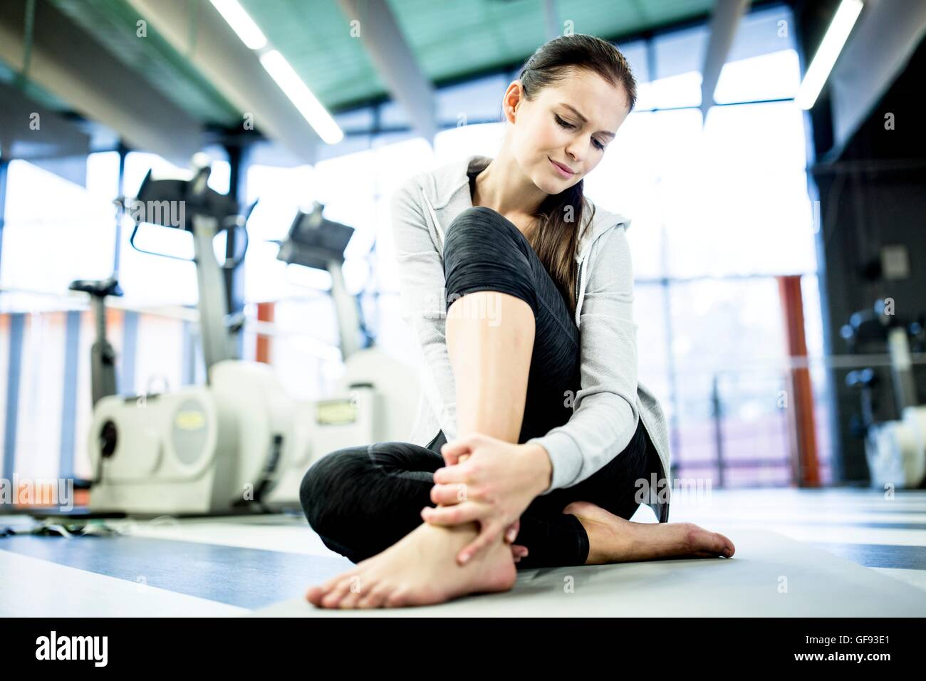 EIGENTUM FREIGEGEBEN. -MODELL VERÖFFENTLICHT. Junge Frau massiert Knöchel bei Schmerzen am Sprunggelenk Stockbild
