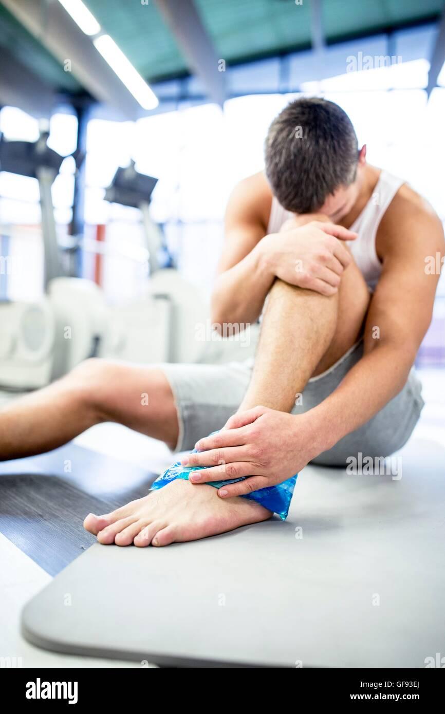 EIGENTUM FREIGEGEBEN. -MODELL VERÖFFENTLICHT. Junger Mann Betrieb Eisbeutel auf verletzten Knöchel im Stockbild