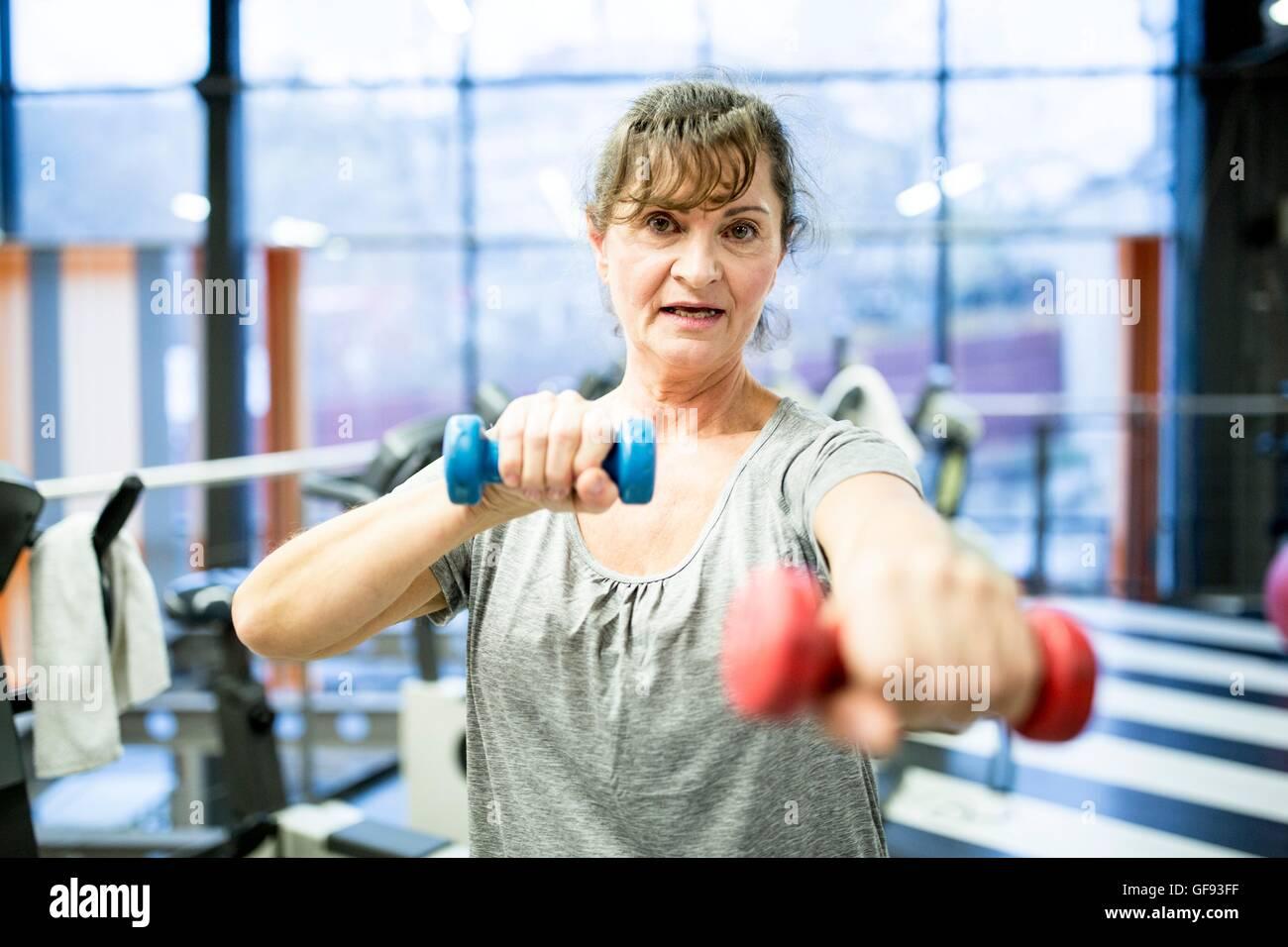 EIGENTUM FREIGEGEBEN. -MODELL VERÖFFENTLICHT. Porträt senior Frau mit Hantel im Fitness-Studio. Stockbild