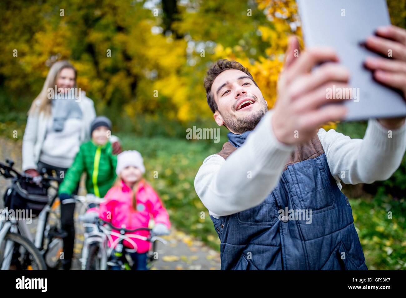 -MODELL VERÖFFENTLICHT. Lächelnder Mann unter Foto der Familie. Stockbild