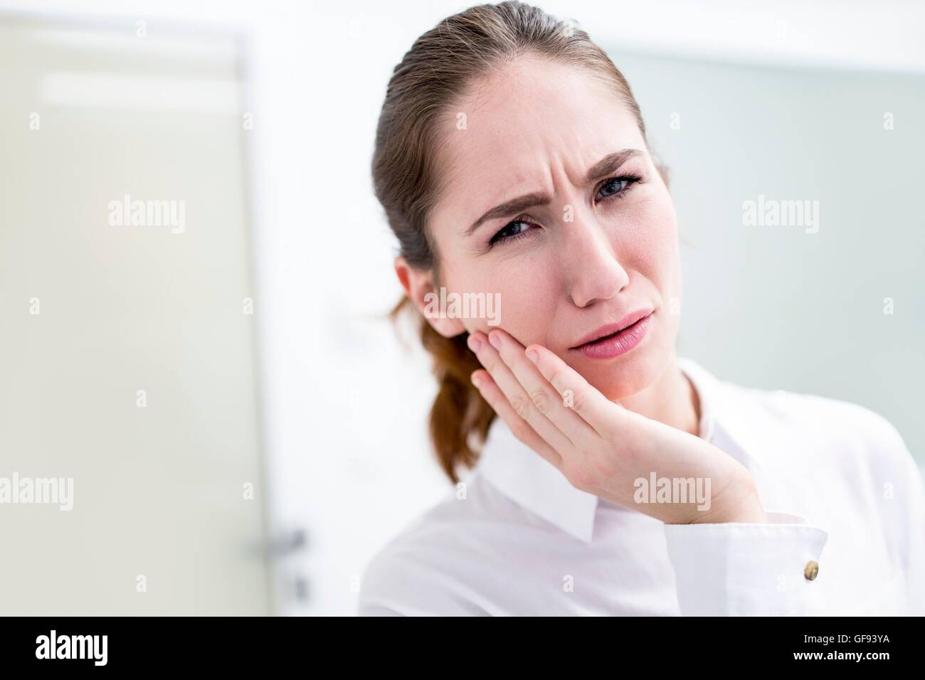 -MODELL VERÖFFENTLICHT. Junge Frau leidet Zahnschmerzen, Studio gedreht. Stockbild