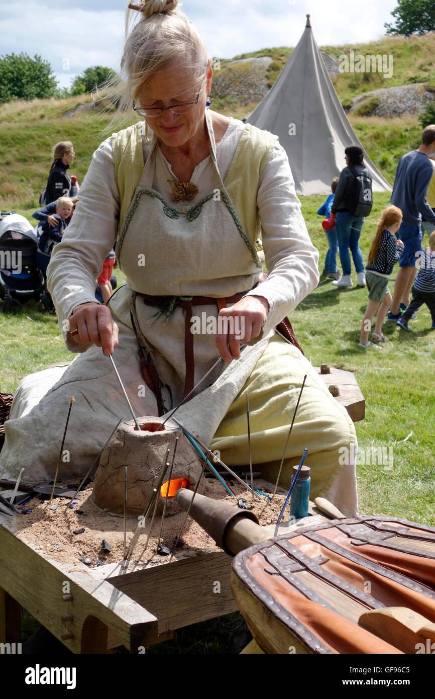 Eine Frau zeigt die frühen mittelalterlichen Glasperlen-Herstellung mit Hilfe von kleinen tragbaren Ton Ofen, Stockbild