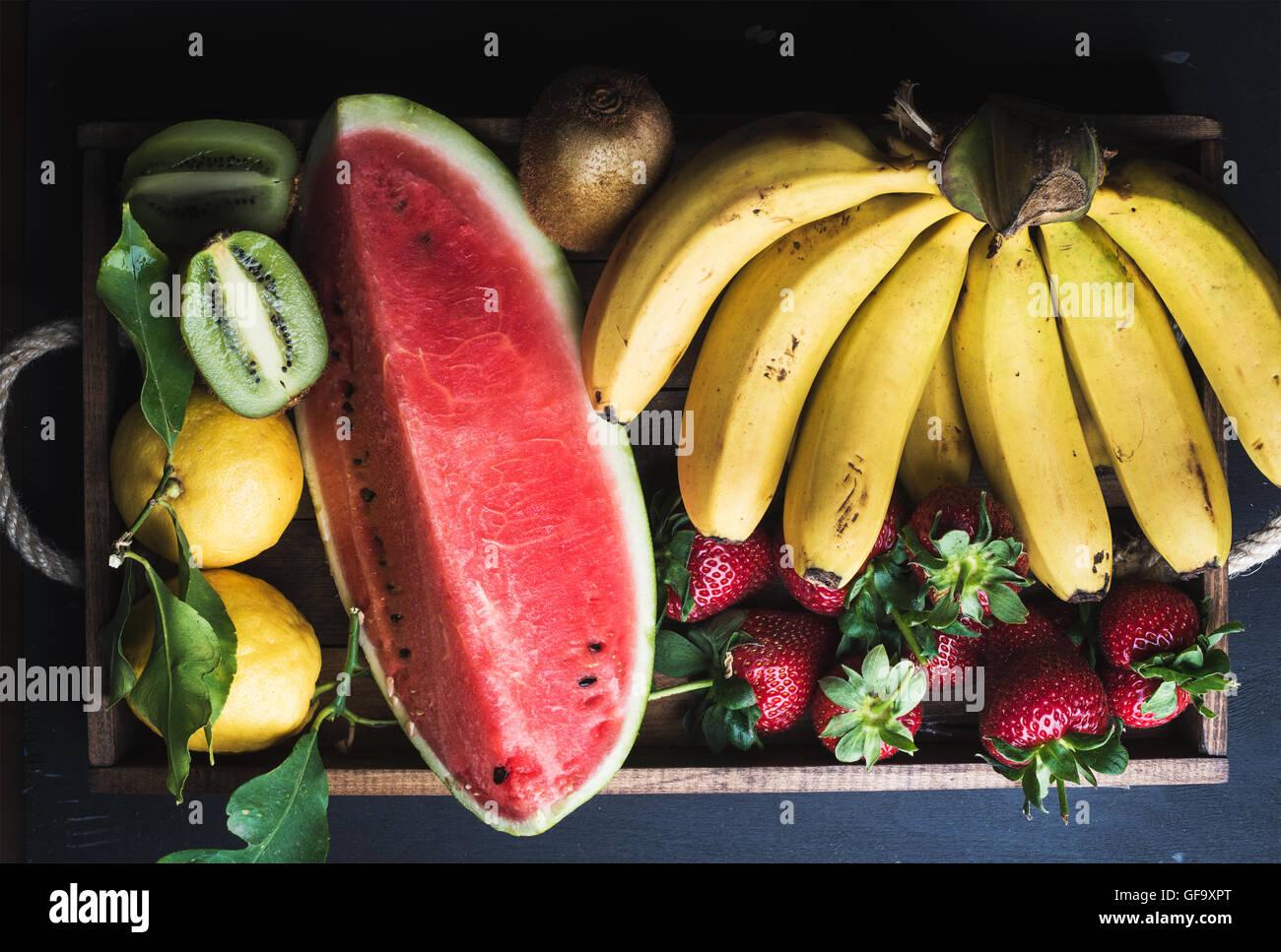 Verschiedene bunte tropische Früchte Auswahl in Holztablett auf dunklem Hintergrund Stockbild