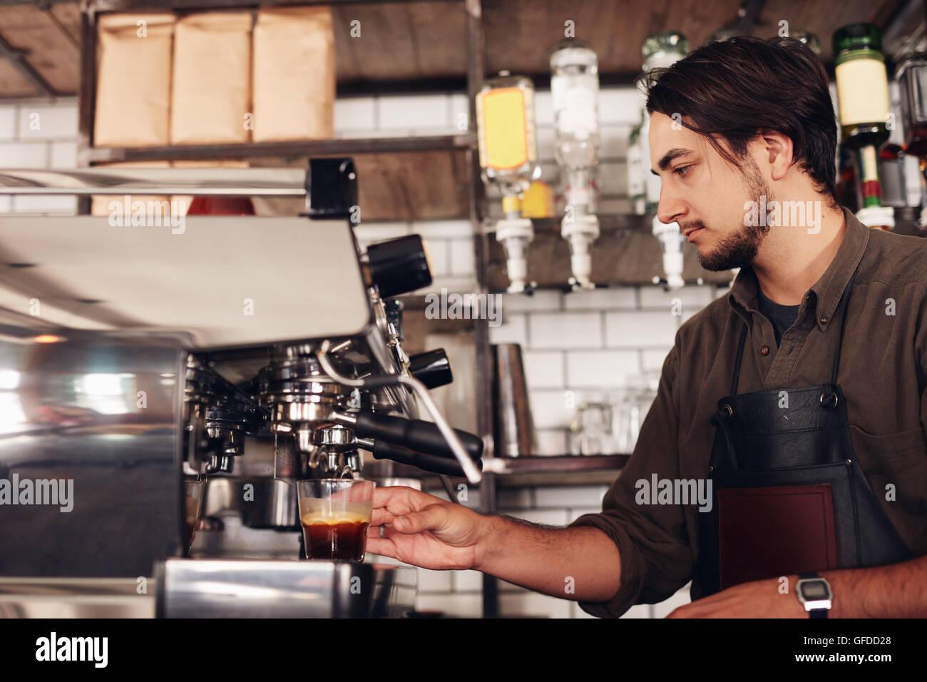 Seitenansicht des männlichen Barista Zubereitung Espresso im Café. Junger Mann in Schürze machen Stockbild