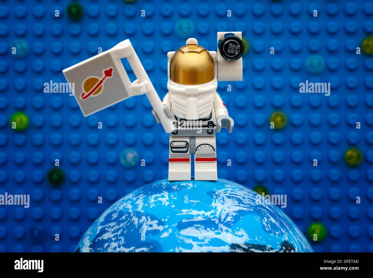 Tambow, Russische Föderation - 6. Juli 2016 Lego Spaceman Minifigur mit Flagge auf Planeten gegen Lego blaue Stockbild