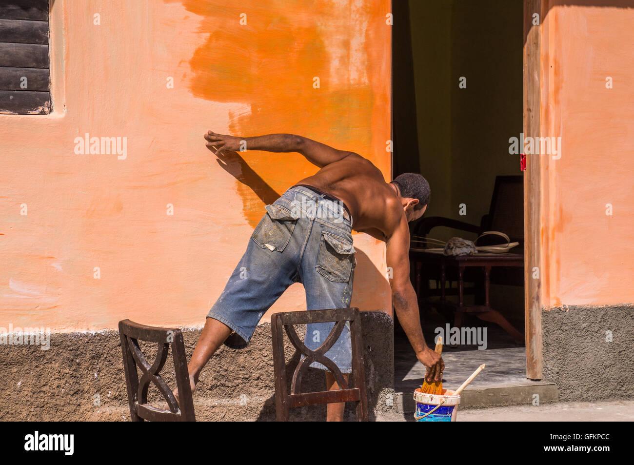 Trinidad, Kuba am 30. Dezember 2015: ein Mann ist eine Wand mit einer leuchtend orange Farbe Malerarbeiten. Dies Stockbild