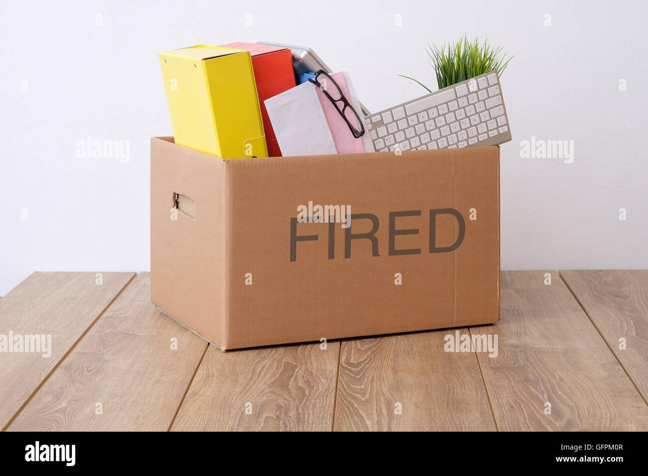 Feuerte Geschäftsmann Box mit Pink-Slip auf Schreibtisch Stockbild
