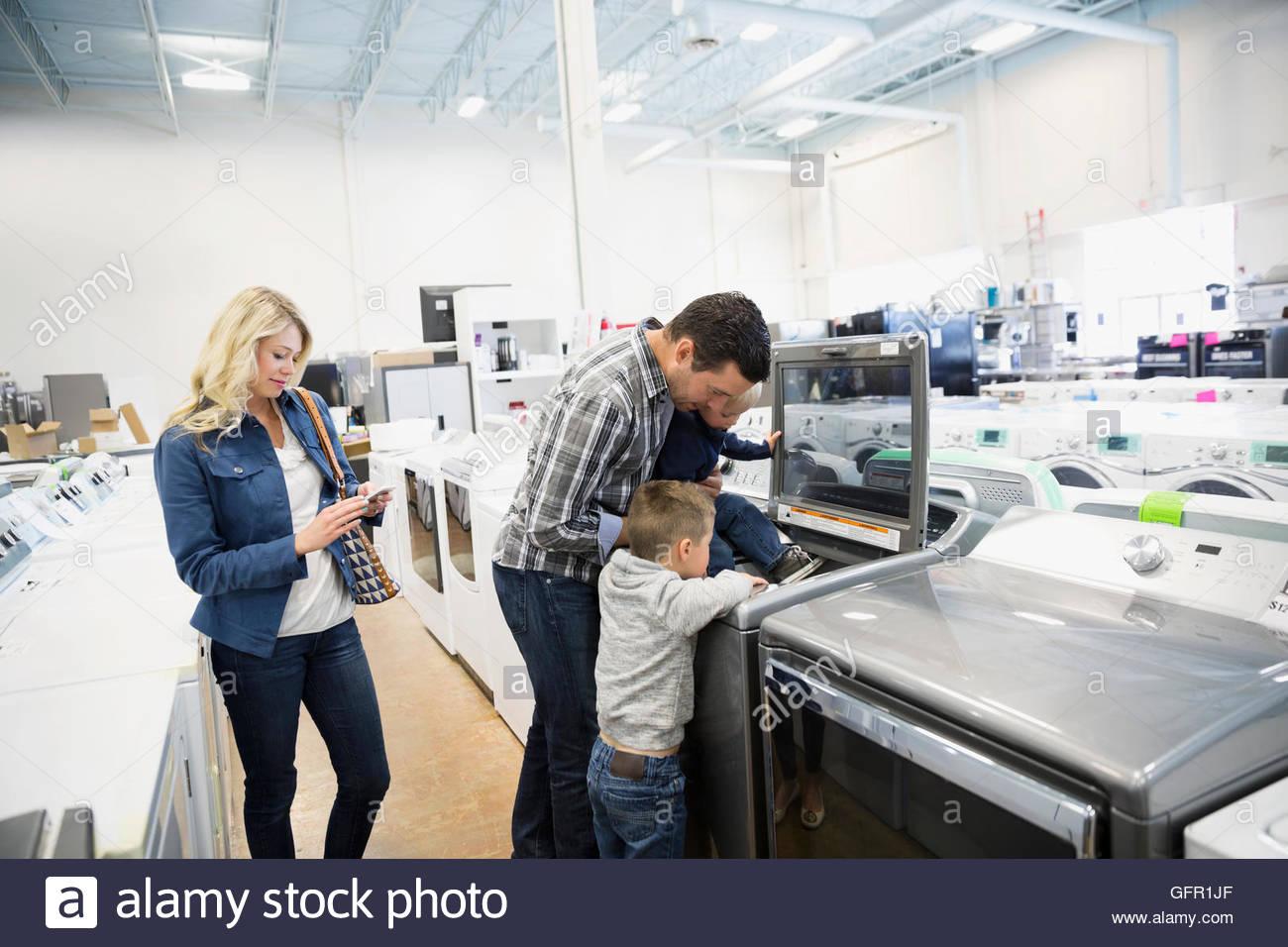 Junge Familie für Waschmaschine im Gerät Store einkaufen Stockbild