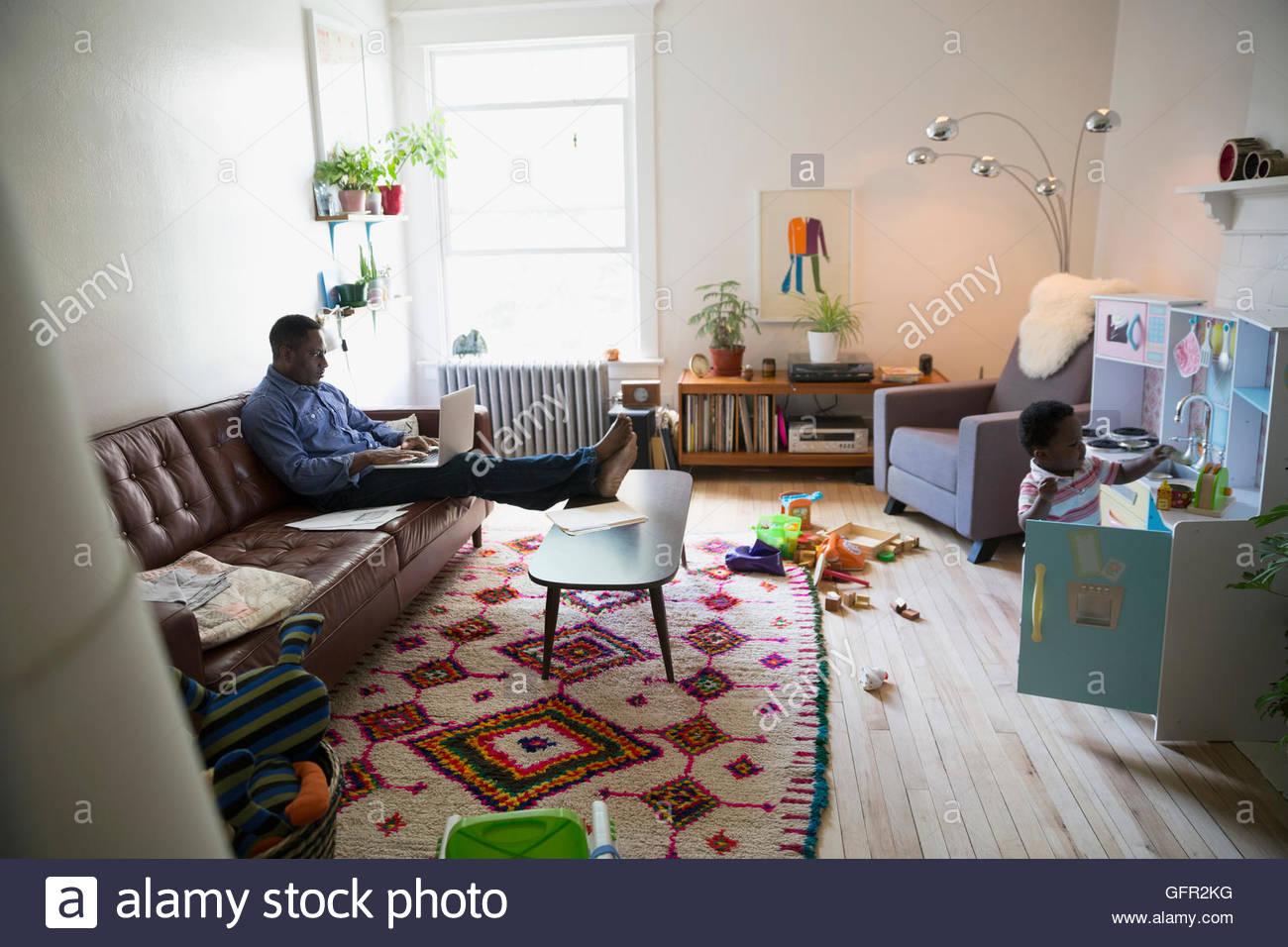Vater mit Laptop in der Nähe von Sohn spielt im Wohnzimmer Stockbild