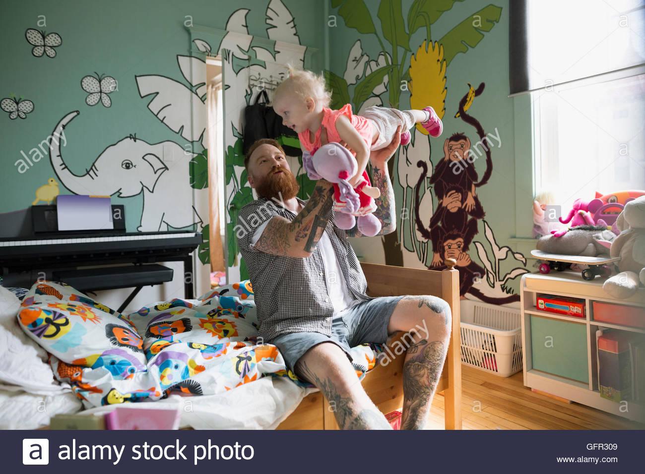 Verspielte Vater Tochter im Schlafzimmer fliegen Stockbild