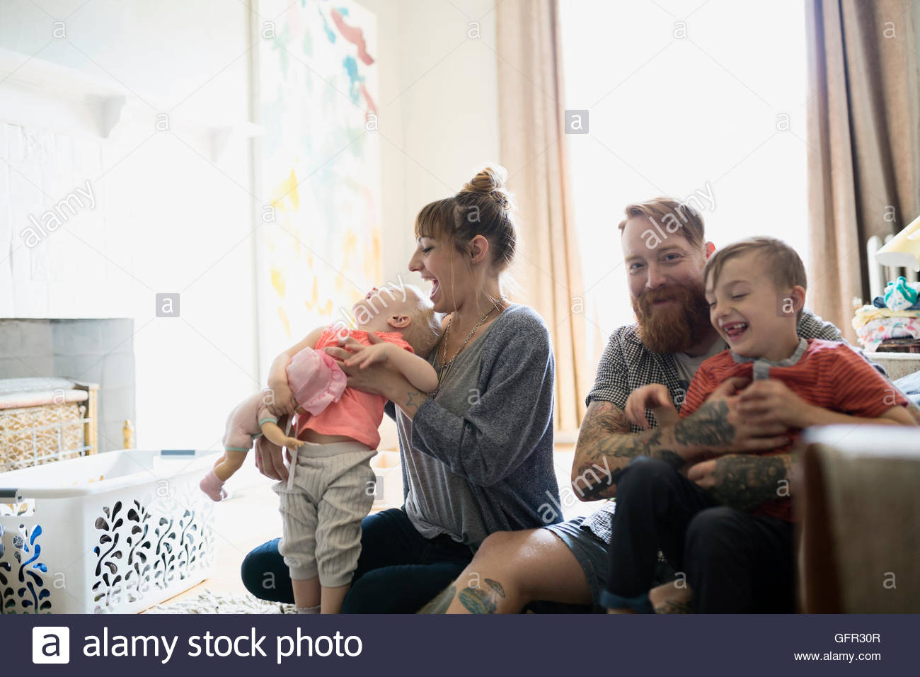 Glückliche junge Familie im Wohnzimmer Stockbild